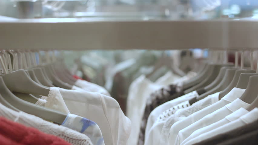 Camera moves along clothes hangers lines with new bright stylish wear under glass  at fashion store | Shutterstock HD Video #24710438
