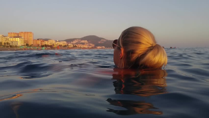 Head and body of woman in sunglasses lying on water of Mediterranean Sea near Mathmutlar, mobile phone video.