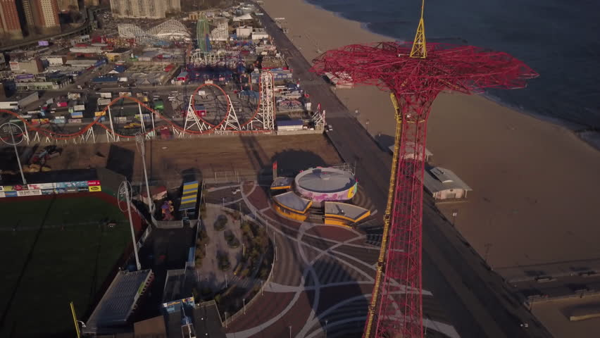 Daytime descending and tilting up shot of Parachute Jump Tower in Coney Island with amusement park in background