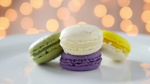 Colorful macarons in white plate with shiny bokeh background