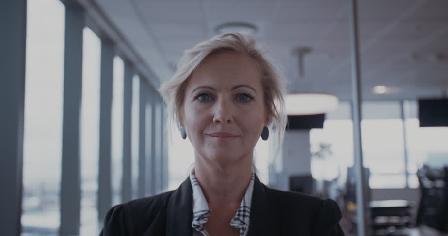 Confident mature businesswoman standing in office. Female manager in office looking at camera and smiling. | Shutterstock HD Video #24741584