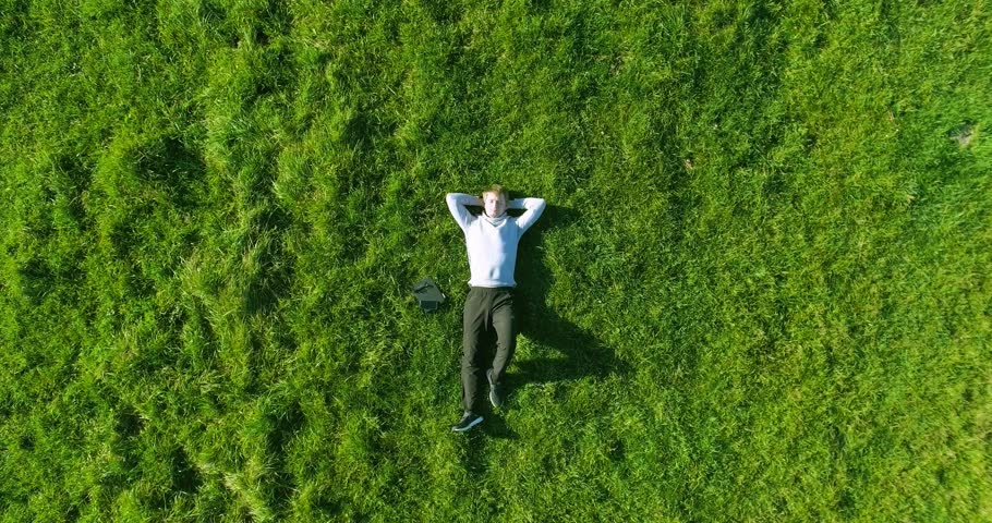 Aerial UHD 4K view. Vertical motion flight over businessman lying on fresh green meadow at sunny summer morning. Top view on handsome relaxing man. | Shutterstock HD Video #24765374