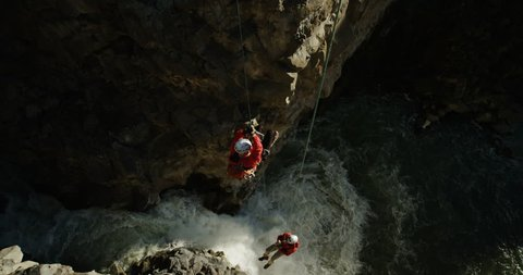 Two men canyoneering ascending up ropes over a beautiful waterfall slow motion