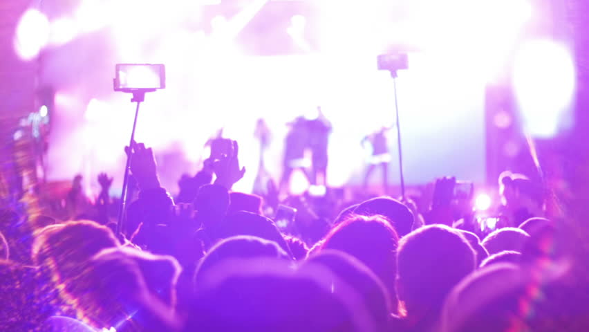 Blurred Concert Crowd at Music Festival. Crowd people dancing Rock concert, weighed, applauds, raises his hands up and photographed, filmed concert on the phones and smartphones. Party People In Action. Crowd