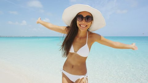 Bikini beach woman happy smiling playful cheerful having fun dancing around. Bikini girl wearing sunglasses excited and joyful. Beautiful sexy mixed race woman having fun on summer travel vacation.