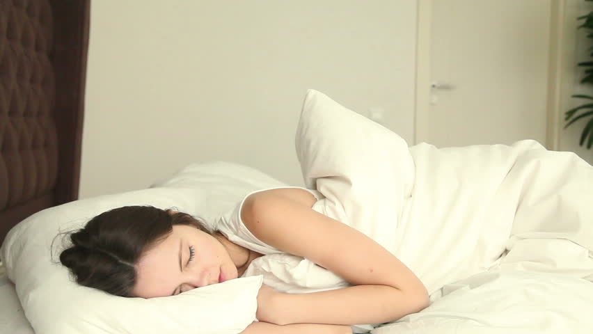 Young beautiful female having problems with her sleep, moving on bed, unable to fall asleep, lying on uncomfortable mattress, waking up with backpain and headache because of insomnia and discomfort