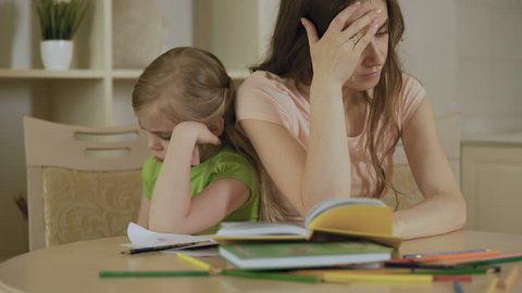Sad mother and daughter having conflict, bored girl refusing to do homework