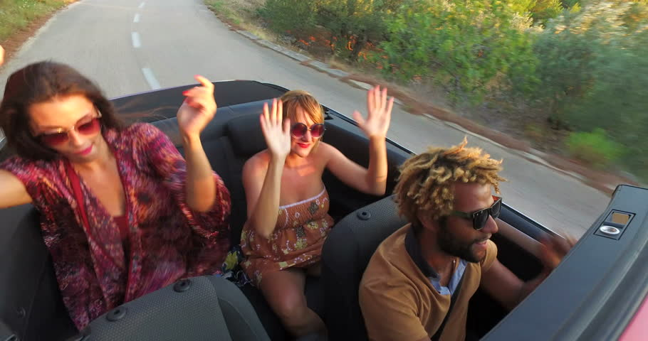 Young party people dancing to music while driving fast in convertible at sunset #24812444