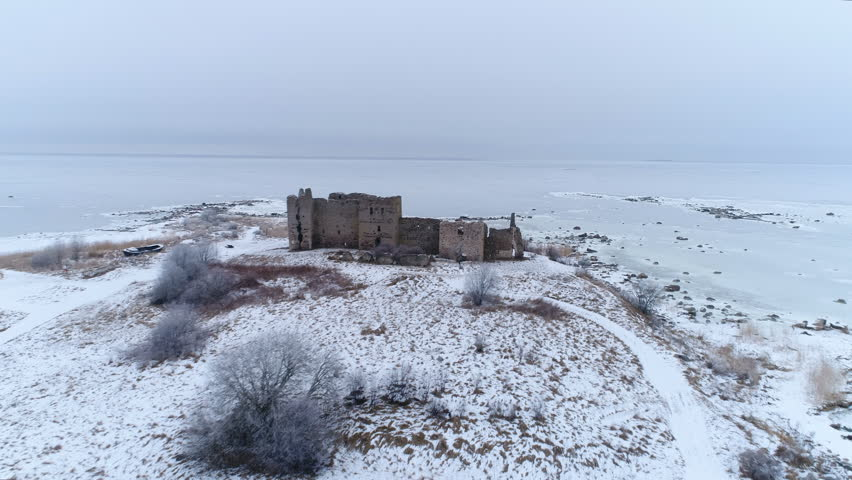 Aerial shot of the old ruined Toolse castle in the middle of the winter with lots of snow on the ground and the frozen sea at the back