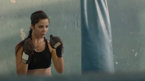 Sport and people, woman, girl, beautiful young female athlete exercising for self-defense in boxing gym. Dolly shot
