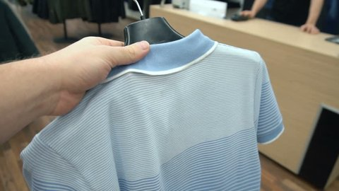 First person view of unrecognizable customer hold blue polo shirt and bring it to shop assistant and purchase with terminal