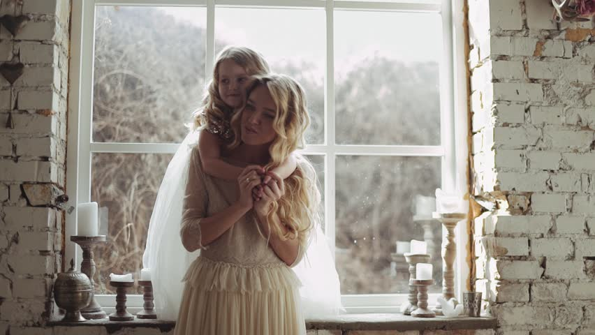 Mother and daughter hugging and playing together. Pretty little girl on beautiful woman's hands. Girls in lace dresses playing in decorated room. Family weekend, beauty day, having fun, love concept. | Shutterstock HD Video #24849566