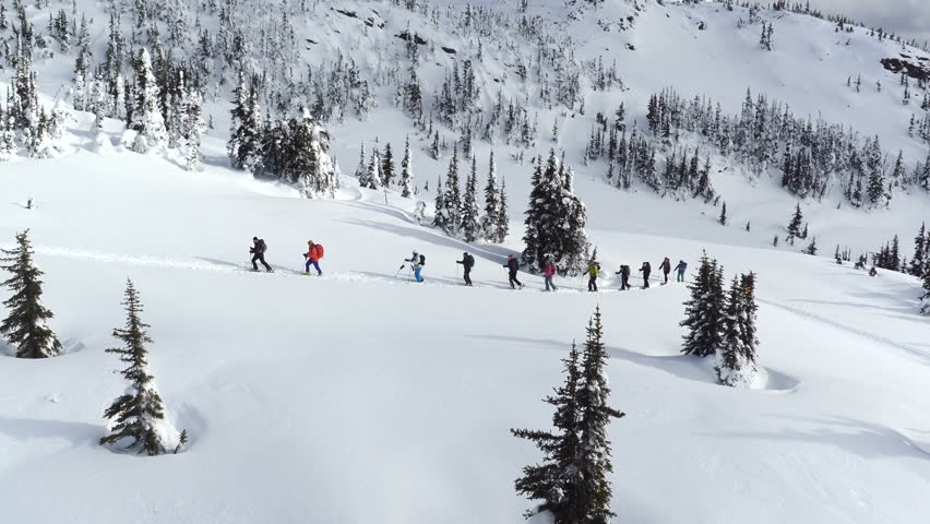 Aerial - Long fly away filming group ski touring skin uphill in a line - Canada