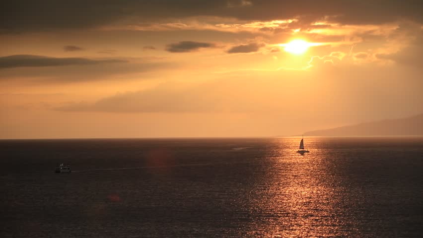 Ocean sunset lit with golden light over the sky and shinig water with a sailboat under sun disc | Shutterstock HD Video #24886889