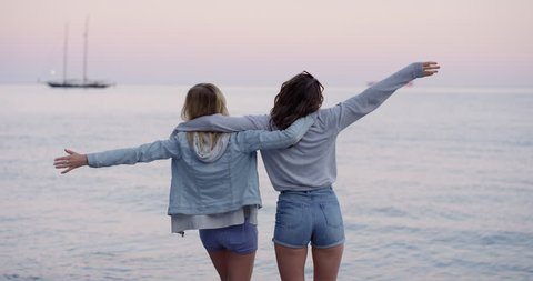 Best friends lifting arms up on beach watching sunset over ocean looking at pink sky wearing denim summer shorts on road trip adventure