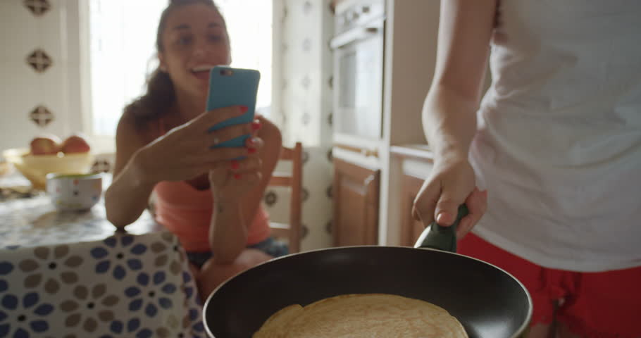 Best Friends making home made Pancakes girl taking photo using smart phone Lifestyle Woman at home sharing on social media