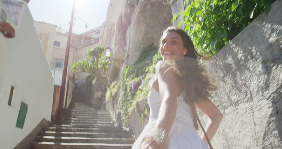 Happy Young Tourist Woman running up through street in Italian town smiling and laughing POV travel concept Amalfi Coast Positano Italy Rear view