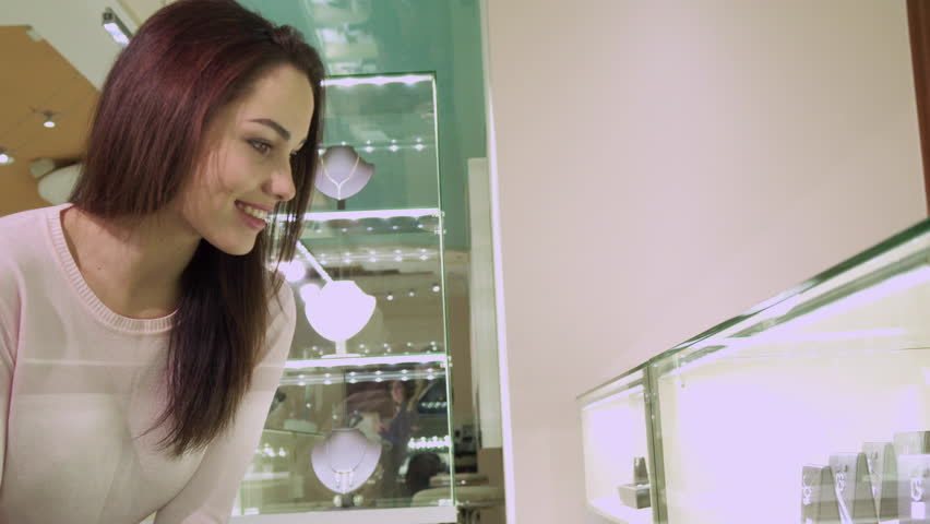 Attractive brunette girl touching her hair at the jewerly shop. Young female customer shopping at the boutique. Side view of pretty caucasian woman standing near the showcase with precious jewels | Shutterstock HD Video #24919757