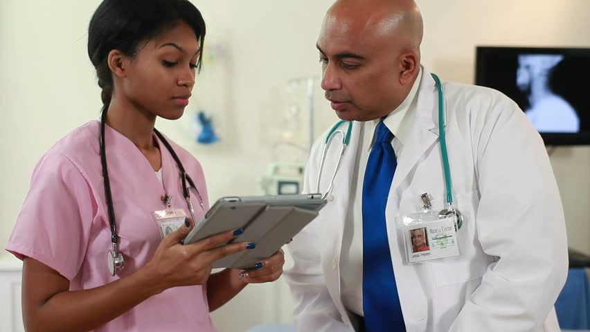 Indian physician with pretty African American nurse using electronic tablet stop discussion and smile for camera.