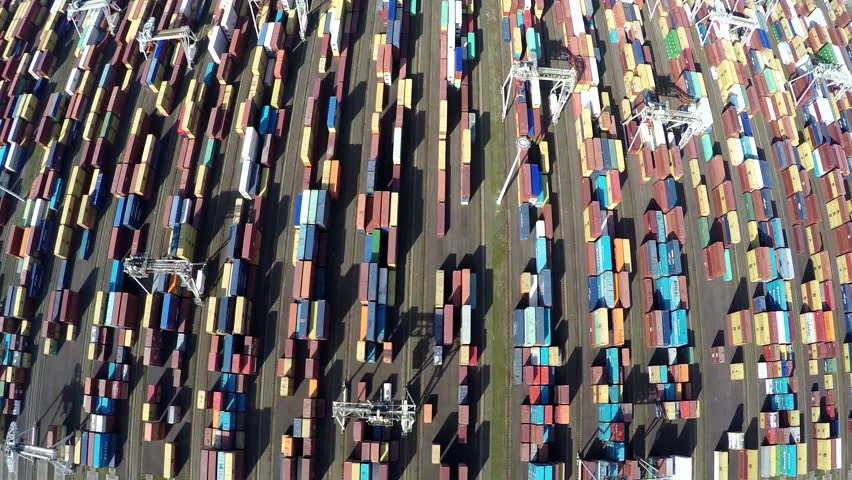 Aerial top down view flying straight over container terminal showing many intermodal containers used for freight transport shipping goods stacked up on each other different colors harbor area 4k