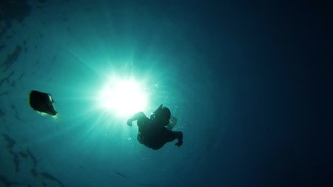 Diver with flippers swimming underwater at turquoise colored sunlight reflection. The diver diving into the seabed. Slow motion effect used.