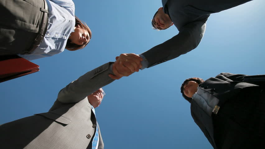 Smiling business teams performing a cross handshake