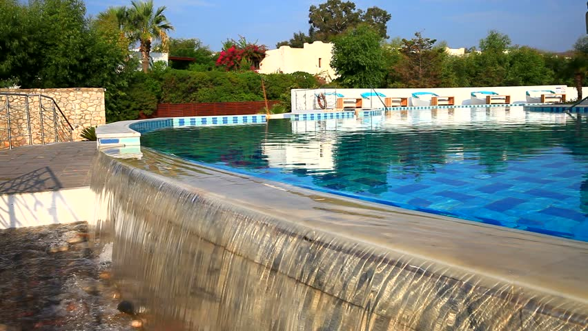 Water Poured From The Swimming Pool Against The Backdrop Of A Southern  Resort With Tropical Plants