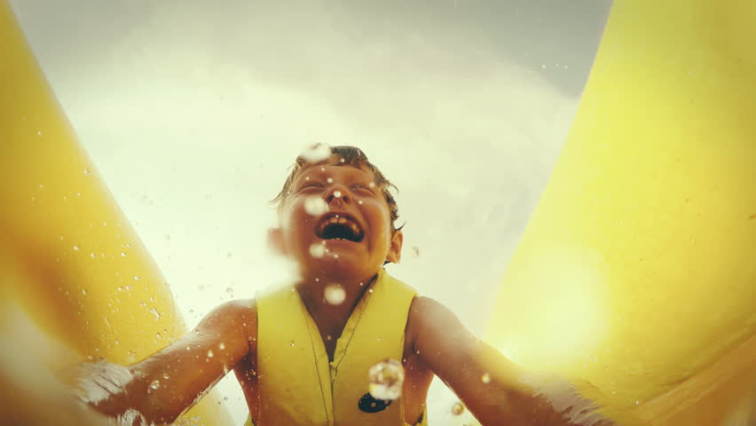 4K action footage: a kid slides down the waterside on his belly screaming from happiness
