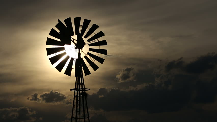 A windmill turning in the wind against a setting sun and storm clouds