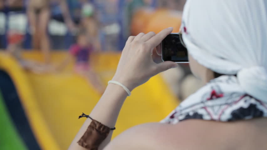 Young woman taking pictures for her family with her smartphone at waterpark   Shutterstock HD Video #25017569
