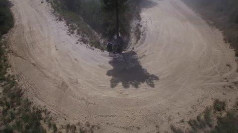 Aerial of subaru wrx sti rally car driving around a hairpin turn slowly