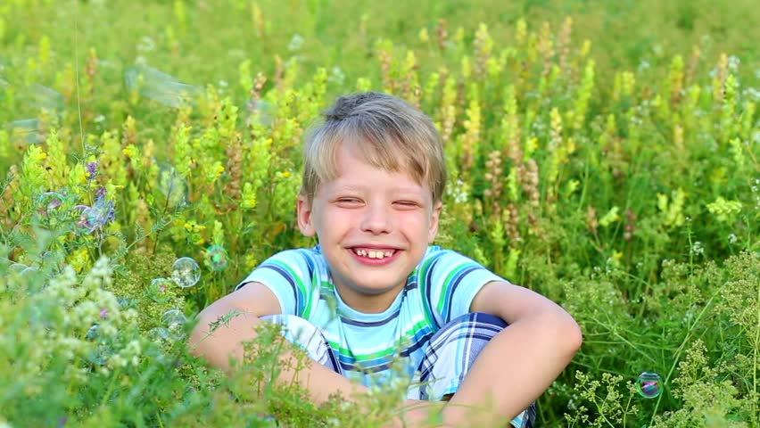 Child sits in green grass with closed eye pretending he does not care about soap bubbles that mother blowing for son. Real time full hd video footage. #25052054