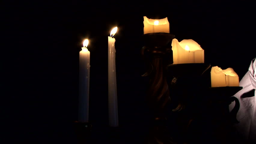 A dolly shot across lit candles ending with a cloaked and masked