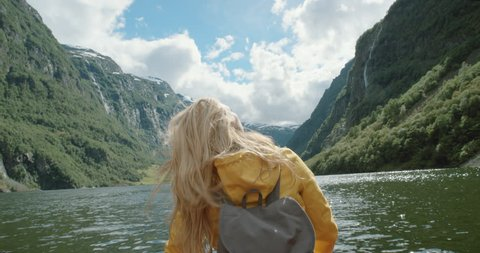 Woman sitting in boat on Fjord Norway hair blowing in wind traveling towards scenic landscape nature background view enjoying vacation travel adventure