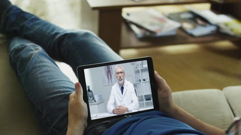 Sick Man Lying on a Couch and Having Video Conversation with His Doctor on a Tablet Computer.