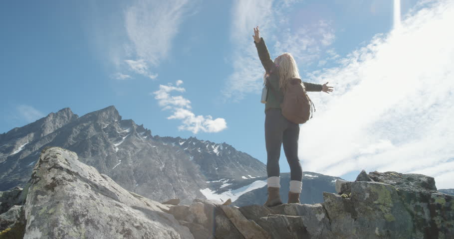 Independent Woman traveller with arms raised on top of mountain looking at view Hiker girl lifting arm up celebrating scenic landscape enjoying vacation travel adventure nature Romsdalen Valley Norway