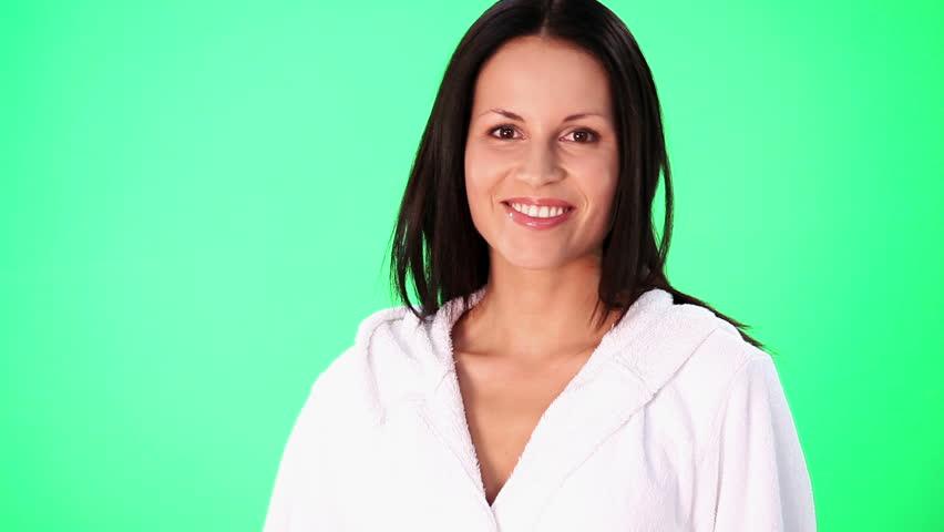 Young beautiful woman wearing bathrobe.  Over green screen background.