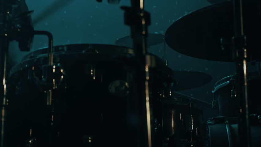 Drummer man playing drums under snow falling. Close up of drumming man snowflakes falling. Man drummer silhouette. Music drums set. Man drum player. Drummer playing drums
