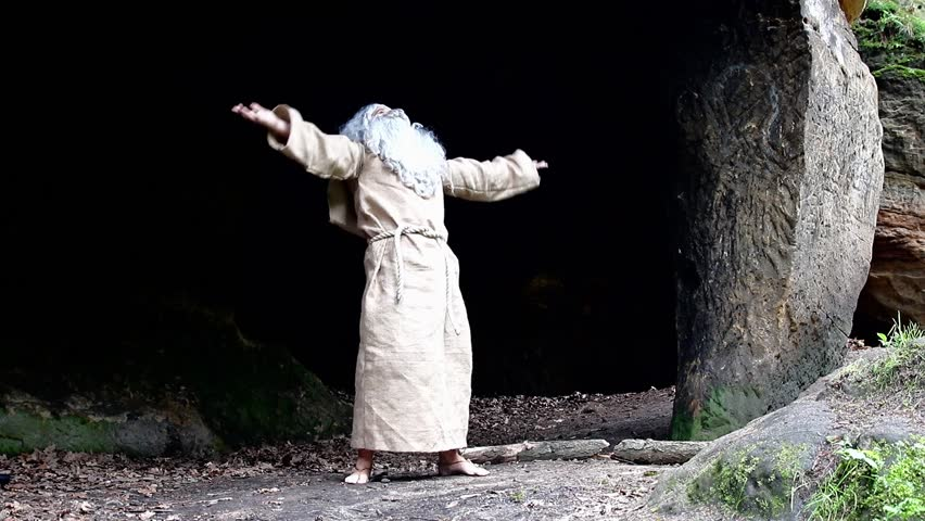 Bearded hermit in a cave is praying. Old monk live in forest.