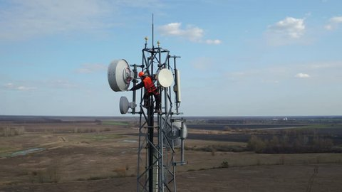 man working on radio telecommunication tower, radio master works at great heights of tv tower, industry of telecommunication engineering, drone flying around outdoor repeater base station tower