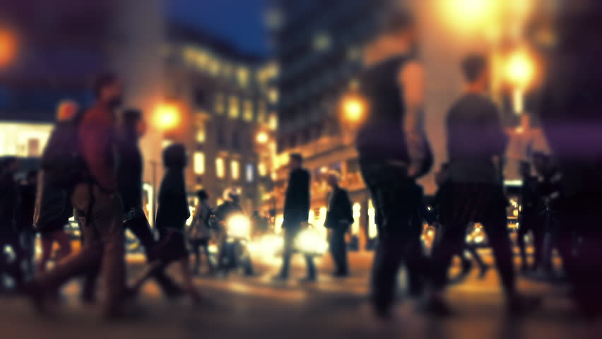 Silhouetted group of pedestrians cross busy big city street at night slomo.100 fps slow motion of a crowd of anonymous backlit pedestrians crossing a busy intersection at night