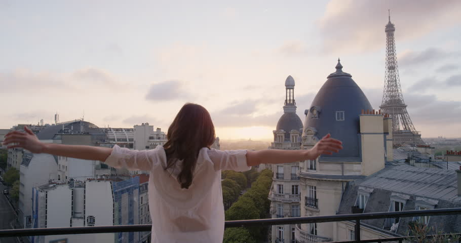 Young tourist woman stretching in morning on hotel balcony with view of Eiffel Tower Paris arms raised enjoying european travel adventure celebrating beautiful city sightseeing exploration