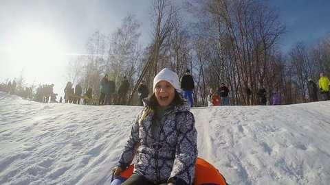 Happy young woman is sledding in the mountain through the snow flies on a springboard in slow motion on sunny day and recording themself on video. 1920x1080