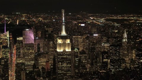 AERIAL HELI SHOT, NO VISIBLE TRADEMARKS Upper Manhattan & Queens borough behind lit up with lights Empire State and Chrysler building. Magical city lights in stunning New York skyline on summer night