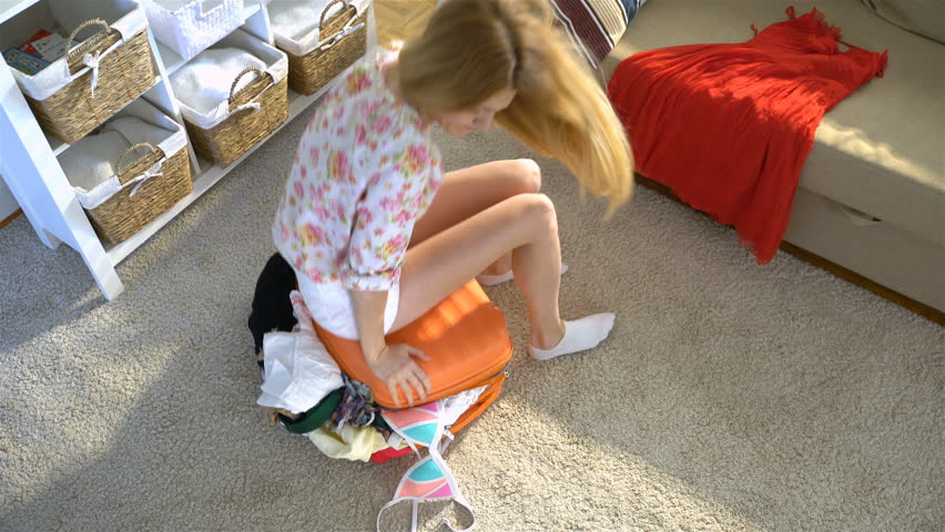 A young woman is trying to close the chock-full orange suitcase. Top view.