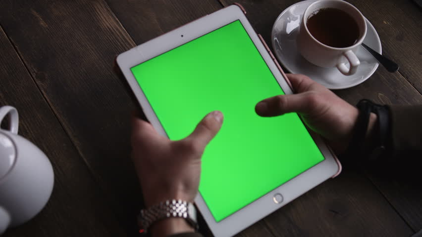 Closeup hands man touching tablet computer with vertical green screen on the table is tea in a cafe | Shutterstock HD Video #25230485