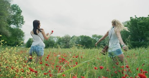 Two young girls wearing denim shorts running through field of wild poppies dancing and spinning in slow motion enjoying european travel adventure