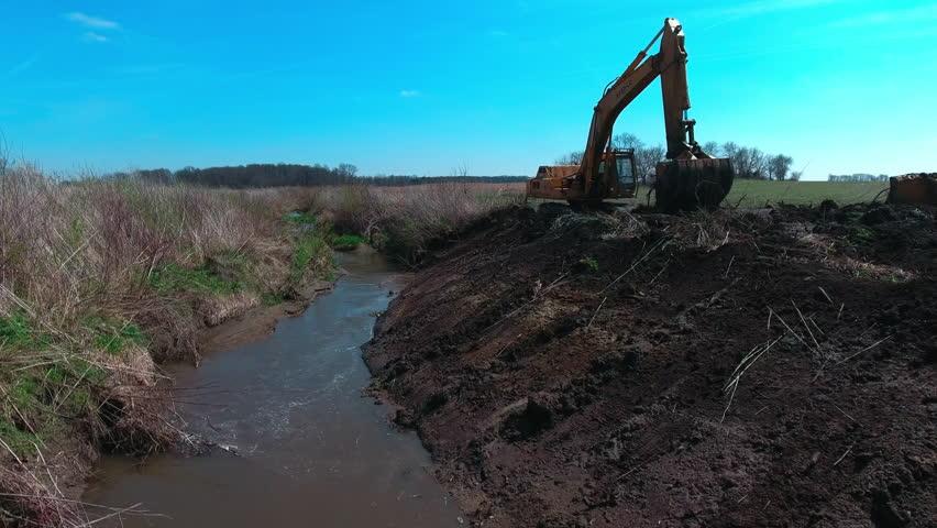 Aerial: Excavator digs in ditch | Shutterstock HD Video #25273844