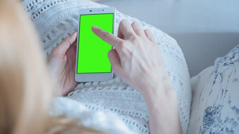 Young Woman laying on a couch uses SmartPhone with pre-keyed green screen. Few types of motion - scrolling up and down, tapping, zoom in and out. Perfect for screen compositing. 10bit ProRes 444.