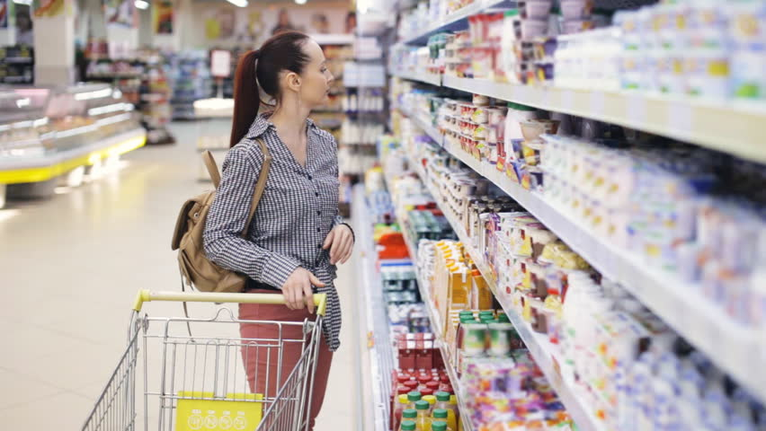 Young woman chooses food in the supermarket | Shutterstock HD Video #25325657